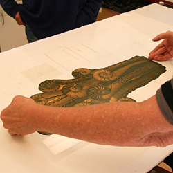 The copper plate is placed on top of the template on the press bed.