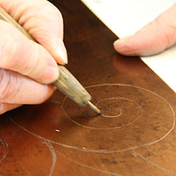 The design is then drawn (in reverse) with an etching-needle with slight pressure. During the drawing, the thin protective hard ground is removed and the copper surface is exposed in these lines.