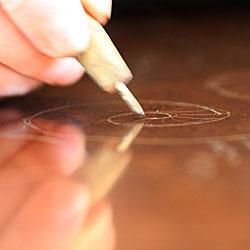 Teckning på kopparplåten sker med etsarnålen med svagt tryck - något spår i själva plåten bör inte uppstå.