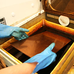 The copper plate is immersed into the bath of ferric chloride solution. The first etching process has started.