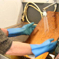 Both sides of the copper plate are rinsed under cold, running water.