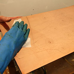 The copper plate is washed with methylated spirit to remove grease.