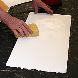 The paper is moistened with a wet sponge for a few hours before the printing start.