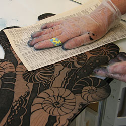 Catharina dries the plate carefully using paper from a telephone directory, which she has discovered is ideal for this purpose.