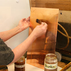 The opposite side of the copper plate is painted with shellac in order to protect it from being etched.