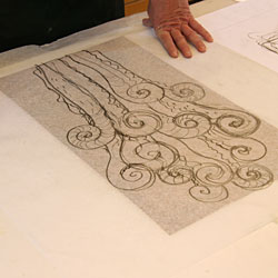 The thin paper with the pencil sketch is placed on the copper plate.