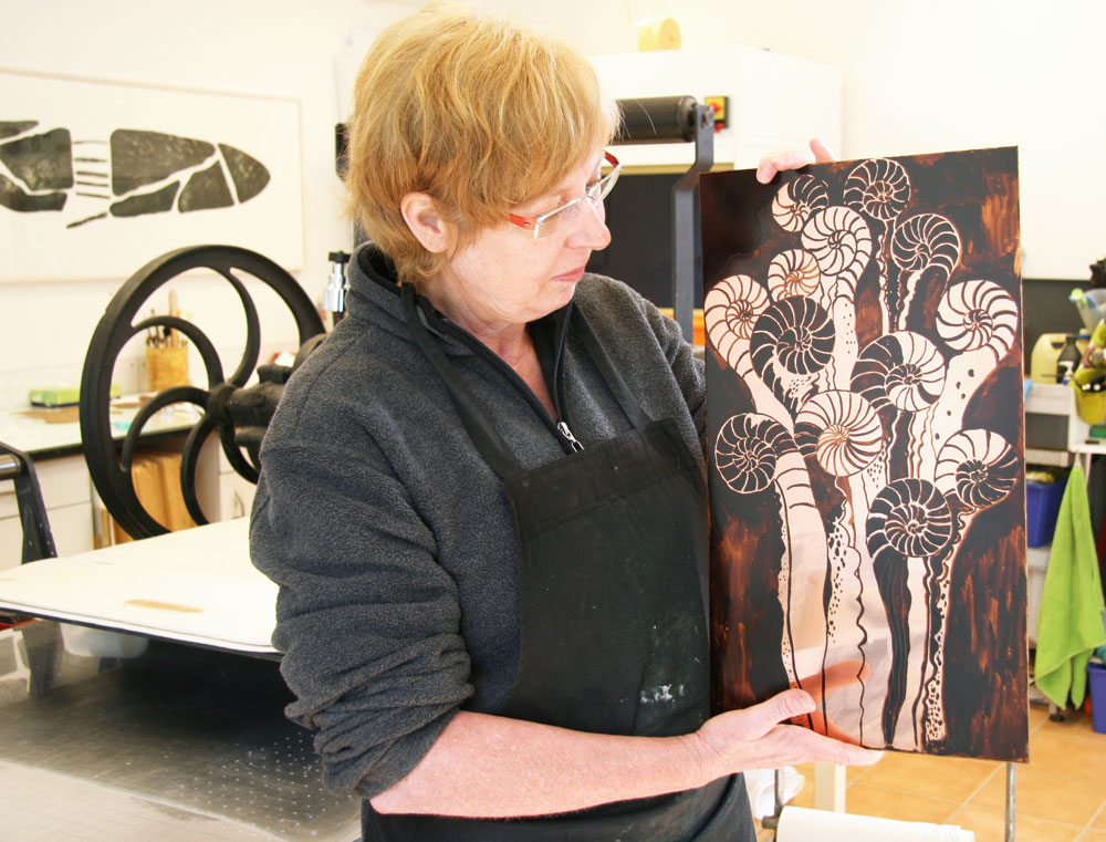 Catharina holds up the pre-painted copper plate which is now ready for the second etching bath.
