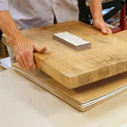När alla blad är på plats mellan papper och kartong så placeras en lätt tyngd upptill.