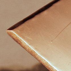 Kopparplåtens kant filas för att kanten ska bli jämn och inte förstöra tryckpapperet och koppartrycksfilten vid tryckningen.