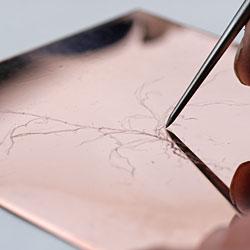 När nålspetsen ristar i plåten bildas ett spår likt en plogfåra kantat av uppskjutande vallar.