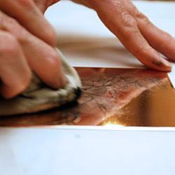 Tryckfärgen arbetas in i plåten med hjälp av ett tygstycke.