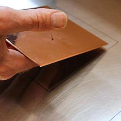 Kopparplåten läggs på plats vid en markering för att trycket ska hamna rätt på papperet.