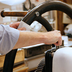 Lars justerar tryckpressens tryck mot tryckbädden.