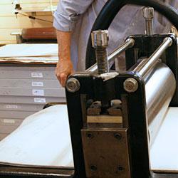 Den åtdragna stålvalsen pressar ner de två yllefiltarna som i sin tur pressar ner det mjuka fuktiga koppartryckspapperet ner i reporna där papperet tar upp färgen.