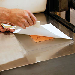 Lars lyfter på papperet för att se...
